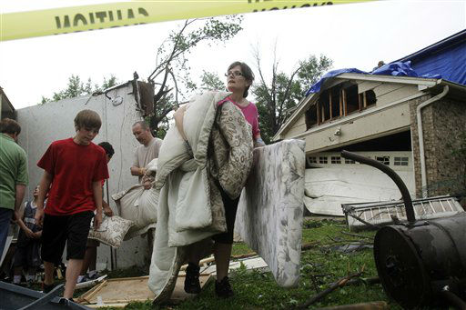 "<div class=""meta ""><span class=""caption-text "">Deeann Powell recovers items from the trailer that a tornado lifted from her driveway to her neighbor's yard two doors down Tuesday, April 03, 2012 in Arlington, Texas. Tornadoes tore through the Dallas area Tuesday, peeling roofs off homes, tossing big-rig trucks into the air and leaving flattened tractor trailers strewn along highways and parking lots. (AP Photo/Kim Johnson Flodin) (AP Photo/ Kim Johnson Flodin)</span></div>"