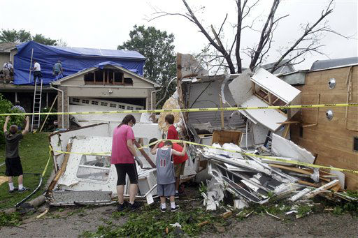 Deeann Powell,  and her children, from left,  Jess, 8, Benjamin, 11, neighbor Christian Brangers, 12 second from right, and son Daniel, 12, right, recover items from their trailer that was carried two doors down to a neighbor&#39;s yard by a tornado in Arlington, Texas Tuesday, April 3, 2012. Tornadoes tore through the Dallas area Tuesday, peeling roofs off homes, tossing big-rig trucks into the air and leaving flattened tractor trailers strewn along highways and parking lots. &#40;AP Photo&#47;Kim Johnson Flodin&#41; <span class=meta>(AP Photo&#47; Kim Johnson Flodin)</span>
