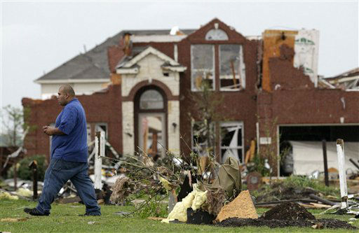 Juan Ventura walks by a badly damaged home as he surveys the tornado damage to his Tuesday, April 3, 2012, in Forney, Texas. Tornadoes tore through the Dallas area Tuesday, peeling roofs off homes, tossing big-rig trucks into the air and leaving flattened tractor trailers strewn along highways and parking lots. &#40;AP Photo&#47;Tony Gutierrez&#41; <span class=meta>(AP Photo&#47; Tony Gutierrez)</span>