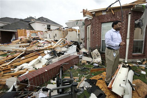 "<div class=""meta ""><span class=""caption-text "">Homeowner Chris Wilson pauses as he talks amongst what remains of his home after a tornado swept through the area Tuesday, April 3, 2012, in Lancaster, Texas. Wilson said no one was home when the tornado came through and he is certain that he will rebuild his home. (AP Photo/Tony Gutierrez) (AP Photo/ Tony Gutierrez)</span></div>"