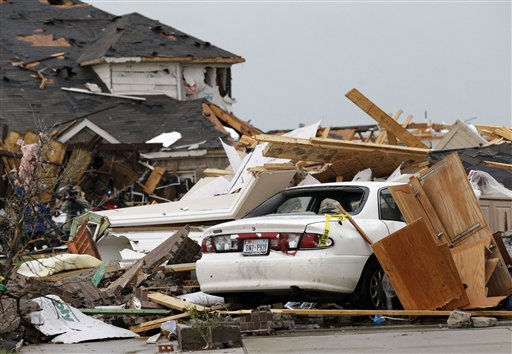Debris on a car and a home damaged by a tornado is seen in the Diamond Creek subdivision Tuesday, April 3, 2012, in Forney, Texas. Tornadoes tore through the Dallas area Tuesday, peeling roofs off homes, tossing big-rig trucks into the air and leaving flattened tractor trailers strewn along highways and parking lots. &#40;AP Photo&#47;Tony Gutierrez&#41; <span class=meta>(AP Photo&#47; Tony Gutierrez)</span>