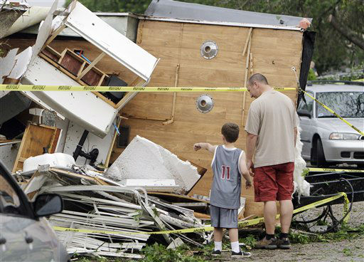 Bill Brangers, right, and Benjamin Powell, 5, left, look at the trailer that a tornado lifted from the Powell&#39;s driveway to a neighbor&#39;s yard two doors down Tuesday, April 03, 2012 in Arlington, Texas. A violent storm spawning tornadoes has touched down in the Dallas-Fort Worth area. Tornadoes tore through the Dallas area Tuesday, peeling roofs off homes, tossing big-rig trucks into the air and leaving flattened tractor trailers strewn along highways and parking lots.  &#40;AP Photo&#47;Kim Johnson Flodin&#41; <span class=meta>(AP Photo&#47; Kim Johnson Flodin)</span>