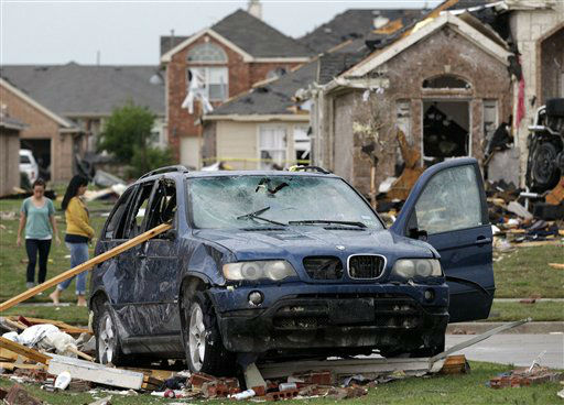 A damaged vehicle is seen as area residents survey the tornado damage to their neighborhood Tuesday, April 3, 2012, in Forney, Texas. Tornadoes tore through the Dallas area Tuesday, peeling roofs off homes, tossing big-rig trucks into the air and leaving flattened tractor trailers strewn along highways and parking lots. &#40;AP Photo&#47;Tony Gutierrez&#41; <span class=meta>(AP Photo&#47; Tony Gutierrez)</span>