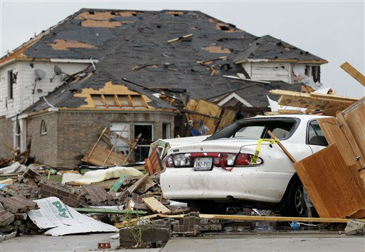 What remains of a home sits on a vehicle, Tuesday, April 3, 2012, in Forney, Texas. Tornadoes tore through the Dallas area Tuesday, peeling roofs off homes, tossing big-rig trucks into the air and leaving flattened tractor trailers strewn along highways and parking lots.  &#40;AP Photo&#47;Tony Gutierrez&#41; <span class=meta>(AP Photo&#47; Tony Gutierrez)</span>