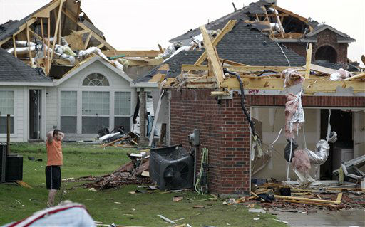"<div class=""meta image-caption""><div class=""origin-logo origin-image ""><span></span></div><span class=""caption-text"">An area resident surveys the damage to a home after a tornado swept through the area 12Tuesday, April 3, 2012, in Forney, Texas. Tornadoes tore through the Dallas area Tuesday, peeling roofs off homes, tossing big-rig trucks into the air and leaving flattened tractor trailers strewn along highways and parking lots. (AP Photo/Tony Gutierrez) (AP Photo/ Tony Gutierrez)</span></div>"