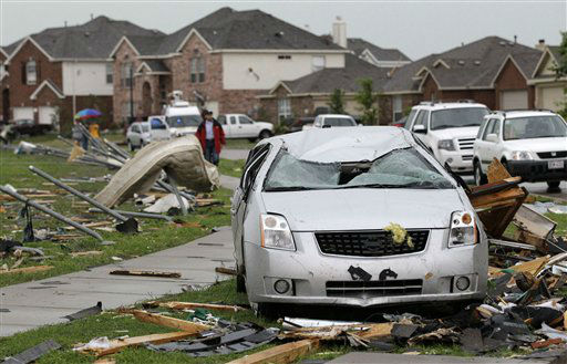 A damaged vehicle stands in sits along a road of damaged homes after a tornado swept through the area Tuesday, April 3, 2012, in Forney, Texas. Tornadoes tore through the Dallas area Tuesday, peeling roofs off homes, tossing big-rig trucks into the air and leaving flattened tractor trailers strewn along highways and parking lots. &#40;AP Photo&#47;Tony Gutierrez&#41; <span class=meta>(AP Photo&#47; Tony Gutierrez)</span>