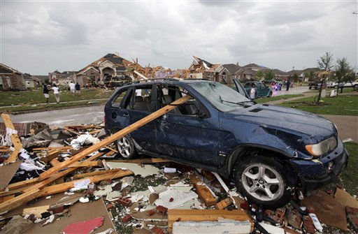 Damage to a vehicle and homes is seen after a tornado swept through the Diamond Creek subdivision Tuesday, April 3, 2012, in Forney, Texas. Tornadoes tore through the Dallas area Tuesday, peeling roofs off homes, tossing big-rig trucks into the air and leaving flattened tractor trailers strewn along highways and parking lots. &#40;AP Photo&#47;Tony Gutierrez&#41; <span class=meta>(AP Photo&#47; Tony Gutierrez)</span>
