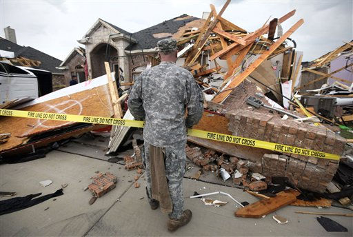 "<div class=""meta image-caption""><div class=""origin-logo origin-image ""><span></span></div><span class=""caption-text"">Texas Army National Guard Cpl. Brock Fischer of Charlie Troop, 3-124 Cav., stands in front of a tornado damaged home in the Diamond Creek subdivision Tuesday, April 3, 2012, in Forney, Texas. Tornadoes tore through the Dallas area Tuesday, peeling roofs off homes, tossing big-rig trucks into the air and leaving flattened tractor trailers strewn along highways and parking lots. (AP Photo/Tony Gutierrez) (AP Photo/ Tony Gutierrez)</span></div>"