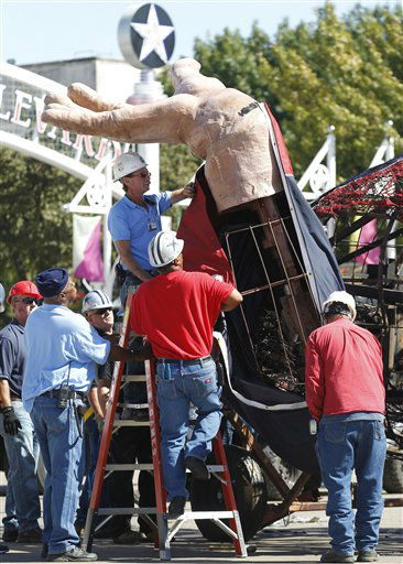 Workers remove the hand from the burned remains of Big Tex at the State Fair of Texas  Friday, Oct. 19, 2012, in Dallas. Big Tex, the metal cowboy whose slow drawl of &#34;Howdy, folks!&#34; made him an icon of the State Fair of Texas for 60 years, was destroyed Friday when flames engulfed his 52-foot-tall frame.. &#40;AP Photo&#47;LM Otero&#41; <span class=meta>(AP Photo&#47; LM Otero)</span>