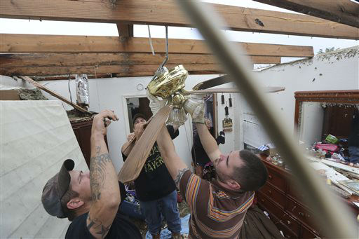 Derrek Girsham, right, Jeremy Hulce, left, and Dustin Seay cut down a fan as they start cleaning up a home that was destroyed by a tornado in Cleburne, Texas, Thursday, May 16, 2013.   <span class=meta>(AP Photo&#47; LM Otero)</span>
