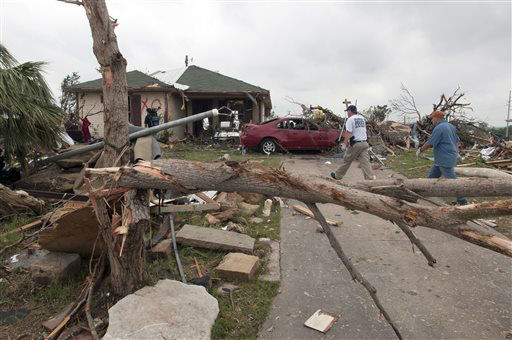 Emergency personnel walk up to a house damaged by a tornado near Granbury, Texas on Thursday, May 16, 2013.  Ten tornadoes touched down in several small communities in Texas overnight, leaving at least six people dead, dozens injured and hundreds homeless. Emergency responders were still searching for missing people Thursday afternoon.   <span class=meta>(AP Photo&#47; Rex C. Curry)</span>