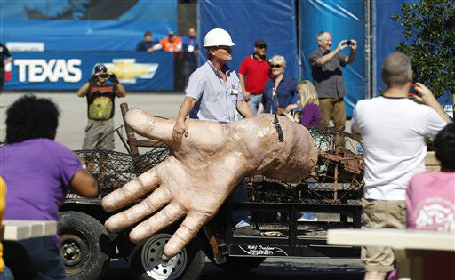 A worker hangs onto the hand of Big Tex as he his carted away after he burned at the State Fair of Texas Friday, Oct. 19, 2012, in Dallas. The iconic structure was destroyed Friday when flames engulfed his 52-foot-tall frame. &#40;AP Photo&#47;LM Otero&#41; <span class=meta>(AP Photo&#47; LM Otero)</span>