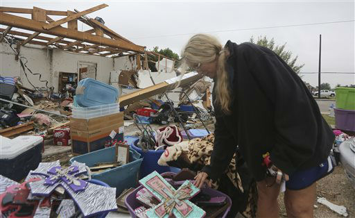 Lisa Montgomery looks at crosses she salvaged from her home that was destroyed by a tornado in Cleburne, Texas, Thursday, May 16, 2013.  Ms. Montgomery rode out the twister the night before in her bathtub with her 10-year-old son and is salvaging items with friends and family helping.  Ten tornadoes touched down in several small communities in Texas overnight, leaving at least six people dead, dozens injured and hundreds homeless. Emergency responders were still searching for missing people Thursday afternoon.  <span class=meta>(AP Photo&#47; LM Otero)</span>