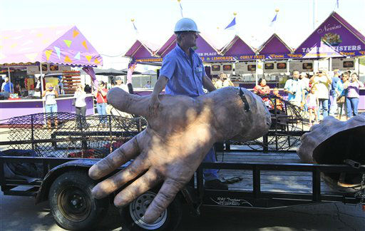 A worker hangs onto the hand of Big Tex as he his carted away after he burned at the State Fair of Texas Friday, Oct. 19, 2012, in Dallas. The iconic structure caught fire and burned this morning.  &#40;AP Photo&#47;LM Otero&#41; <span class=meta>(AP Photo&#47; LM Otero)</span>