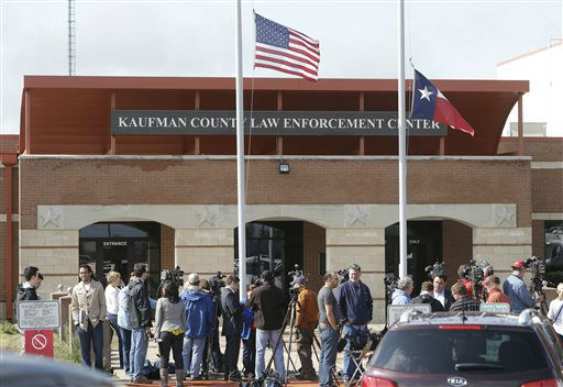 Media gather at the Kaufman County Law Enforcement Center in Kaufman, Texas, Sunday, March 31, 2013, in advance of a news conference, as the U.S. and Texas state flags fly at half-staff. On Saturday, Kaufman County District Attorney Mike McLelland and his wife, Cynthia, were murdered in their home.   <span class=meta>(AP Photo&#47; Mike Fuentes)</span>