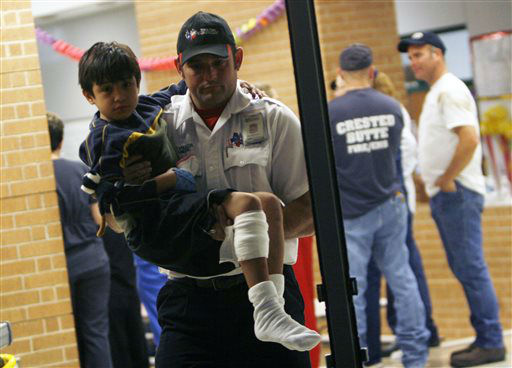 "<div class=""meta image-caption""><div class=""origin-logo origin-image ""><span></span></div><span class=""caption-text"">A young injured boy is carried to an awaiting ambulance in Granbury, Texas, on Wednesday May 15, 2013.  A rash of tornadoes slammed into several small communities in North Texas overnight, leaving at least six people dead, dozens more injured and hundreds homeless. The violent spring storm scattered bodies, flattened homes and threw trailers onto cars.  (AP Photo/ Mike Fuentes)</span></div>"
