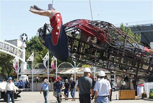 The burned remains of Big Tex are lowered from his display at the State Fair of Texas  Friday, Oct. 19, 2012, in Dallas.  Big Tex, the metal cowboy whose slow drawl of &#34;Howdy, folks!&#34; made him an icon of the State Fair of Texas for 60 years, was destroyed Friday when flames engulfed his 52-foot-tall frame. &#40;AP Photo&#47;LM Otero&#41; <span class=meta>(AP Photo&#47; LM Otero)</span>