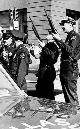 "<div class=""meta ""><span class=""caption-text "">Police officers with guns ready look up the building where the shot came from that killed U.S. President John F. Kennedy while he was riding in an open limousine through downtown Dallas, Texas, on November 22, 1963.  (AP Photo) (AP Photo/ XCB)</span></div>"