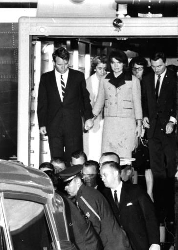 First Lady Jacqueline Kennedy, her dress stained with blood, stands with Attorney General Robert F. Kennedy, holding her hand, as they watch the casket of her slain husband, President John F. Kennedy, placed in an ambulance at Andrews Air Force Base, Md., near Washington, November 22, 1963.  The body of the president was flown from Dallas, Texas, where he was fatally shot earlier in the day.  At right are Evelyn Lincoln, glasses, and Kenneth O&#39;Donnell of the White House staff.  Mrs. Lincoln was the late president&#39;s personal secretary.  &#40;AP Photo&#41; <span class=meta>(AP Photo&#47; XTH)</span>