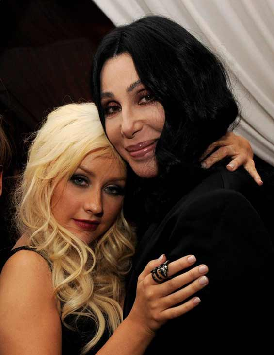Cher and Christina Aguilera pose together while...