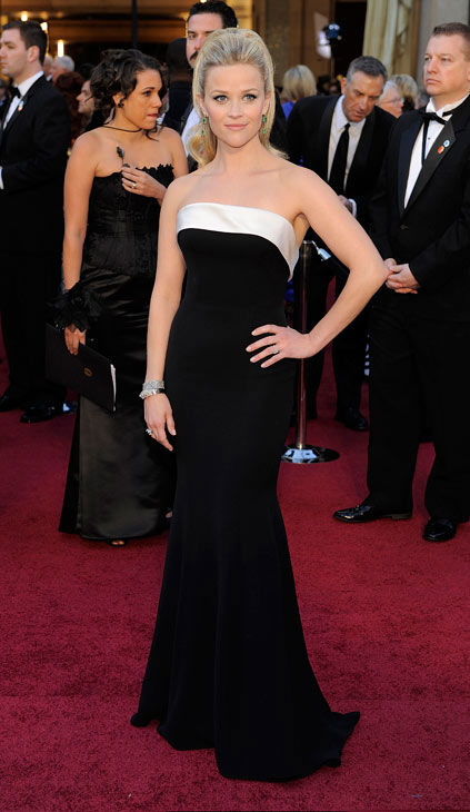 Reese Witherspoon arrives before the 83rd Academy Awards on Sunday, Feb. 27, 2011, in the Hollywood section of Los Angeles.  She is wearing a simple, floor length black and white Giorgio Armani Prive gown.