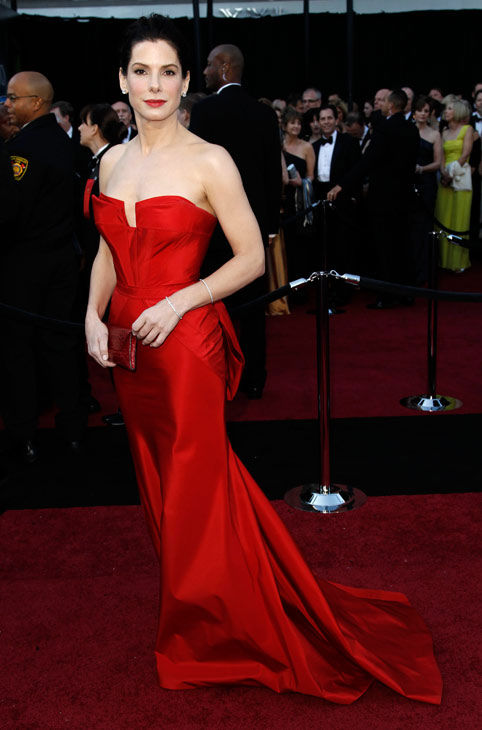 Sandra Bullock, who won the 2010 'Best Actress' Oscar for her role in 'The Blind Side' arrives before the 83rd Academy Awards on Sunday, Feb. 27, 2011, in the Hollywood section of Los Angeles.  She is wearing a bright red Vera Wang strapless gown.