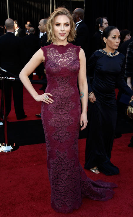 Actress Scarlett Johansson arrives before the 83rd Academy Awards on Sunday, Feb. 27, 2011, in the Hollywood section of Los Angeles.  She is wearing a maroon floral-printed, slimming Dolce and Gabbana dress that features a peek-a-boo chest section.