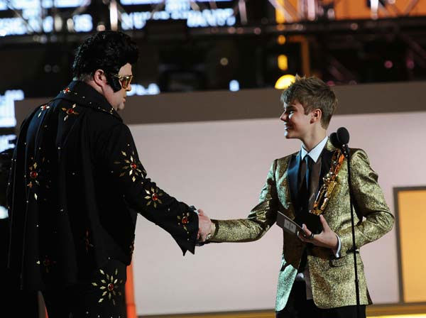 "<div class=""meta ""><span class=""caption-text "">'Modern Family' star Eric Stonestreet dons a black Elvis costume and shakes Justin Bieber's hand at the 2011 Billboard Music Awards in Las Vegas on Sunday, May 22, 2011. (ABC Photo/ Kevin Mazur)</span></div>"