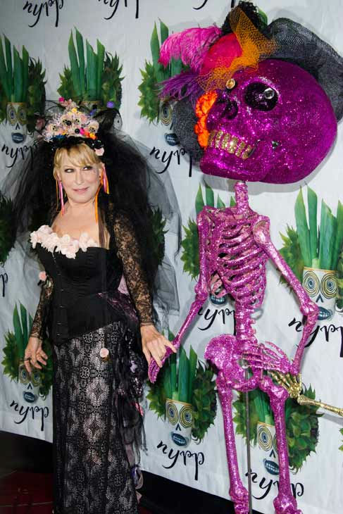 Bette Midler poses alongside a skeleton statue...