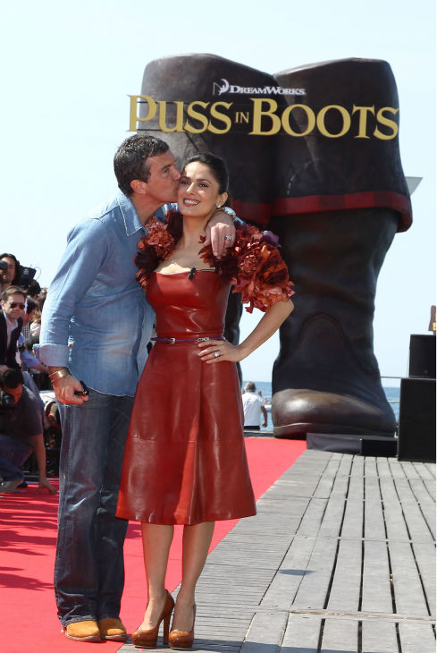 Actor Antonio Banderas kisses actress Salma Hayek as they attend the 'Puss in Boots' Photocall at Carlton Beach during the 64th Cannes Film Festival on May 11, 2011 in Cannes, France.