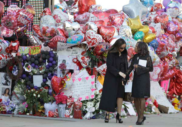 Two women pause near a memorial display before funeral services for singer Whitney Houston at the New Hope Baptist Church in Newark, N.J.,  Saturday, Feb. 18, 2012.  <span class=meta>(AP Photo&#47; Mel Evans)</span>
