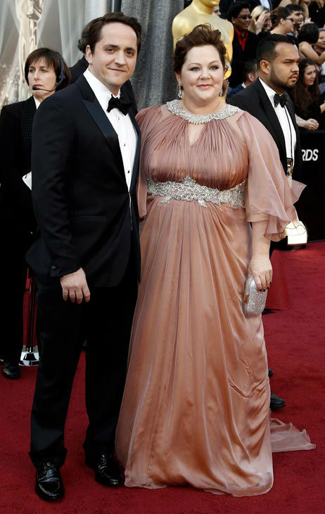 Ben Falcone, left, and Melissa McCarthy arrive before the 84th Academy Awards on Sunday, Feb. 26, 2012, in the Hollywood section of Los Angeles.  McCarthy, who was nominated for her supporting role in &#39;Bridesmaids,&#39; wore a dusty mauve Marina Rinaldi gown with flutter sleeves and silver embellishments along the neckline and high waist.  She also wore Chopard chandelier earrings featuring pear-shape white diamonds &#40;10 carats&#41; set in platinum, accented with pink diamonds pave-set in rose gold, and a brilliant-cut pink tourmaline cocktail ring &#40;24 carats&#41;, set with over 500 white diamonds in white gold.   <span class=meta>(AP Photo&#47; Matt Sayles)</span>