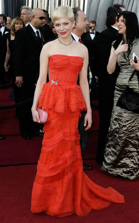 Michelle Williams arrives before the 84th Academy Awards on Sunday, Feb. 26, 2012, in the Hollywood section of Los Angeles. Michelle Williams donned a red, strapless Louis Vuitton peplum gown with a structured bustier and a tiered floor-length skirt. <span class=meta>(AP Photo&#47; Matt Sayles)</span>