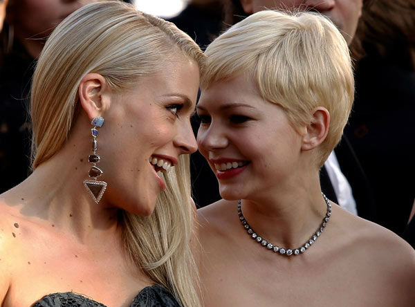 Busy Philipps, left, and Michelle Williams arrive before the 84th Academy Awards on Sunday, Feb. 26, 2012, in the Hollywood section of Los Angeles. Williams sported a persimmon-red Louis Vuitton strapless dress with a structured bustier and a tiered floor-length skirt. She rounded out the outfit in a bubble-gum pink crocodile clutch and a darling bow brooch on her waist. <span class=meta>(AP Photo&#47; Joel Ryan)</span>