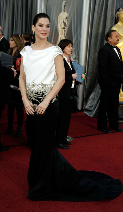 Sandra Bullock arrives before the 84th Academy Awards on Sunday, Feb. 26, 2012, in the Hollywood section of Los Angeles. The Oscar-winning actress, who was also a presenter at the event, donned a Marchesa floor-length gown with wreath details on the draped shoulders and the dropped waist. The dress featured a low, scooping back and slight train. Bullock wore her hair slicked back in a high ponytail. <span class=meta>(AP Photo&#47; Matt Sayles)</span>