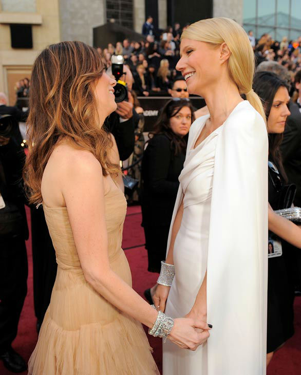 Kristen Wiig, left, and Gwyneth Paltrow arrive before the 84th Academy Awards on Sunday, Feb. 26, 2012, in the Hollywood section of Los Angeles. Paltrow wore a white Tom Ford gown with a cape detail and Wiig donned a strapless nude J. Mendel dress with a sweetheart neckline and tiered details down the full-length skirt. <span class=meta>(AP Photo&#47; Chris Pizzello)</span>