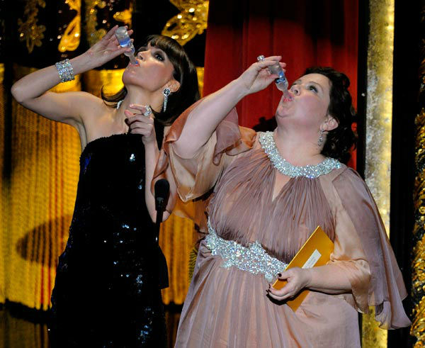 Members of the cast of 'Bridesmaids' Rose Byrne and Melissa McCarthy drink a toast to Martin Scorsese as they present an award during the 84th Academy Awards on Sunday, Feb. 26, 2012, in the Hollywood section of Los Angeles.