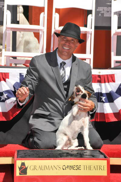 Uggie, the 10-year-old Jack Russell terrier who starred in 'The Artist,' was honored with a retirement party and a paw print ceremony at Grauman's Chinese Theatre on June 25, 2012. Uggie is seen with his trainer Omar Von Muller at the event. <br /><br />'