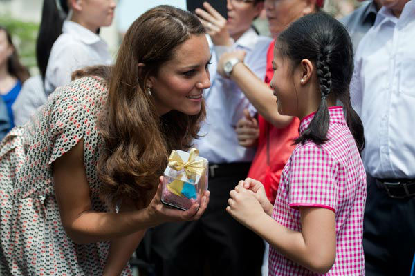 Catherine, the Duchess of Cambridge, receives a gift from a girl during her visit to Strathmore Green, a precinct in Queenstown, a residential district of Singapore, Wednesday, Sept. 12, 2012. Britain&#39;s Prince William and his wife Catherine arrived in Singapore on September 11 to kick off a nine-day Southeast Asian and Pacific tour marking Queen Elizabeth II&#39;s Diamond Jubilee.Middleton wore a cream silk patterned pleated skirt and top, designed by Singapore-based designer Raoul.  <span class=meta>(AP Photo&#47; NICOLAS ASFOURI)</span>