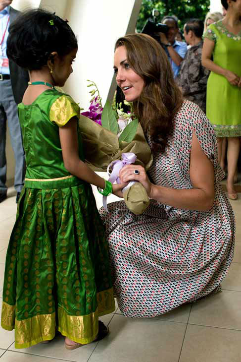 Kate, the Duchess of Cambridge, receives flowers from a girl during her visit to Strathmore Green, a precinct in Queenstown, a residential district of Singapore on Wednesday, Sept. 12, 2012. Britain&#39;s Prince William and his wife Kate, the Duke and Duchess of Cambridge, are on a nine-day tour of the Far East and South Pacific. Middleton wore a cream silk patterned pleated skirt and top, designed by Singapore-based designer Raoul.  <span class=meta>(AP Photo&#47; Nicolas Asfouri)</span>