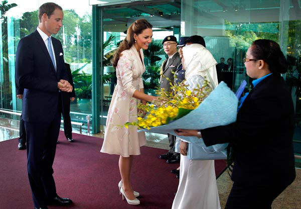 Prince William, the Duke of Cambridge, left, watches his wife Kate, the Duchess of Cambridge, center, receives flowers upon arrival at the VIP terminal of Changi International Airport on Tuesday, Sept. 11, 2012 in Singapore. The British royal couple is on an official three-day trip to Singapore.Middleton wore a Jenny Packham pink knee-length dress with an orchid pattern with off-white L.K. Bennett Sledges.  <span class=meta>(AP Photo&#47; Wong Maye-E)</span>