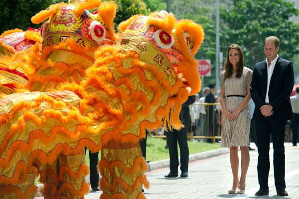 Britain&#39;s Prince William and his wife Kate, the Duke and Duchess of Cambridge, are welcomed by a lion dance performance during their visit to Strathmore Green, a precinct in Queenstown, a residential district of Singapore on Wednesday, Sept. 12, 2012. Britain&#39;s royal couple are on a nine-day tour of the Far East and South Pacific.  Middleton wore a cream silk patterned pleated skirt and top, designed by Singapore-based designer Raoul.  <span class=meta>(AP Photo&#47; Nicolas Asfouri)</span>