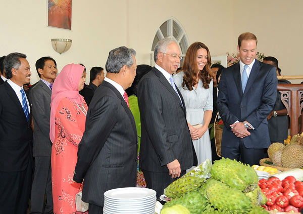 In this photo released by Malaysia's Information Department, Malaysian Prime Minister Najib Razak, third from right, introduces local fruits to Britain's Prince William, right, and his wife Kate, second from right, the Duke and Duchess of Cambridge.