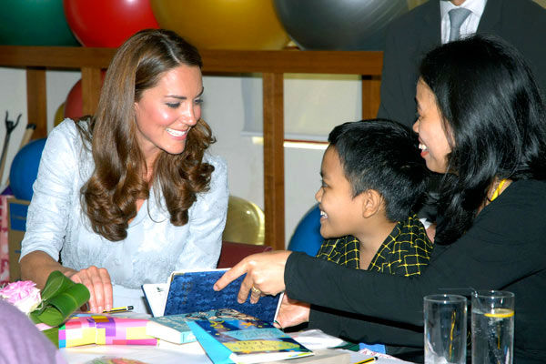 In this photo released by Malaysia&#39;s Information Department, Britain&#39;s Kate, left, the Duchess of Cambridge, speaks to a boy at Hospis Malaysia in Kuala Lumpur, Malaysia, Thursday, Sept. 13, 2012. Britain&#39;s Prince William and his wife Kate, the Duke and Duchess of Cambridge, are in Malaysia for a three-day visit as part of a tour to mark Queen Elizabeth II&#39;s Diamond Jubilee. Middleton wore a Jenny Packham bespoke eucalyptus silk crepe shirt dress with a French lace bodice. <span class=meta>(AP Photo&#47; Uncredited)</span>