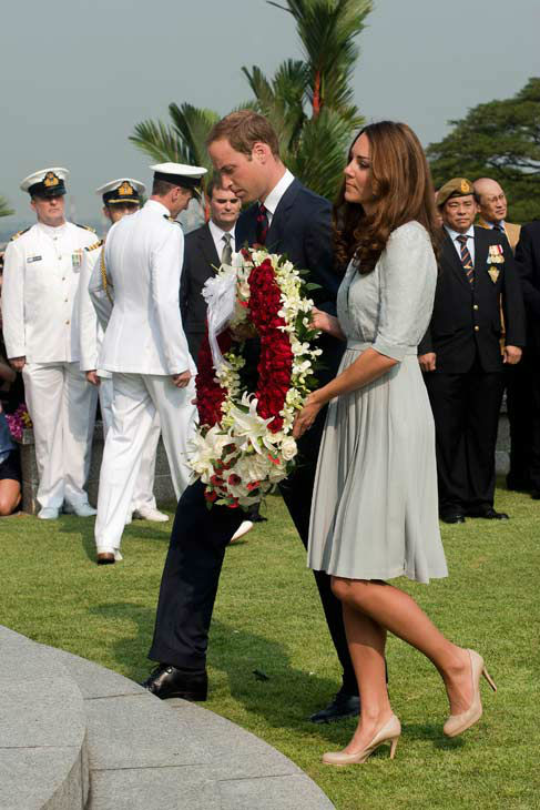 Britain&#39;s Prince William and his wife Kate, the Duke and Duchess of Cambridge, carry a wreath together to pay their respects to the war dead of World War II during a visit to the Kranji War Memorial in Singapore Thursday, Sept. 13, 2012. Middleton wore a Jenny Packham bespoke eucalyptus silk crepe shirt dress with a French lace bodice. <span class=meta>(AP Photo&#47; Nicolas Asfouri)</span>