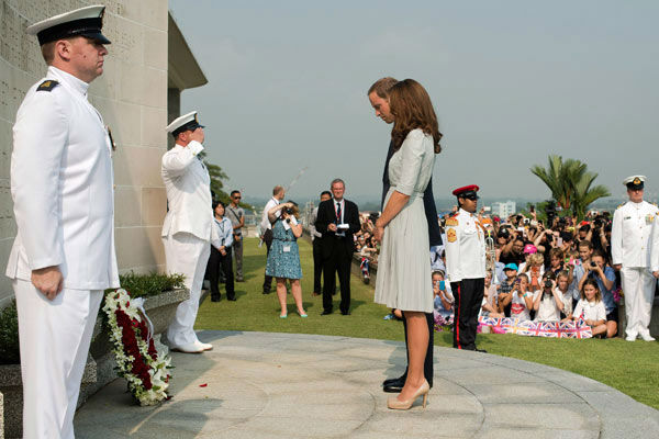 Britain&#39;s Prince William and his wife Kate, the Duke and Duchess of Cambridge, pause for a moment of silence after laying a wreath to pay their respects to the war dead of World War II during a visit to the Kranji War Memorial in Singapore Thursday, Sept. 13, 2012. Middleton wore a Jenny Packham bespoke eucalyptus silk crepe shirt dress with a French lace bodice. <span class=meta>(AP Photo&#47; Nicolas Asfouri)</span>