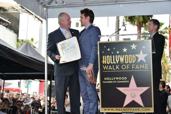 Actor James Franco (R) and Councilmember Tom LaBonge speak onstage during a ceremony honoring James Franco with a star on The Hollywood Walk of Fame on March 7, 2013 in Hollywood, California.