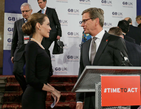 Angelina Jolie, left, in her role as UN envoy, talks to German Foreign Minister Guido Westerwelle, right, following a news conference regarding sexual violence against women in conflict during the G8 Foreign Ministers meeting in London on Thursday, April,