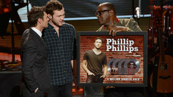 "<div class=""meta image-caption""><div class=""origin-logo origin-image ""><span></span></div><span class=""caption-text"">Phillip Phillips took home the title of 'American Idol' during the show's 11th season, despite not considering himself worthy of the coveted honor.  'Honestly, man, I didn't think I'd even make it to see the judges. I have no shame in saying it - I'm not a great singer,'  he told reporters backstage following the being crowned the 'American Idol.'  'I just love having fun up on stage, jamming with the guys and just playing good music, man. I like getting the crowd into it. Music's fun, dude. It takes away a lot of things that's going around.' Phillips released his debut album, 'The World From The Side Of The Moon,' which premiered at number four on the Billboard 200 albums chart.  Phillips has released two singles from his album, 'Home' and 'Gone, Gone, Gone,' the latter of which was used during season 12 of 'Idol' when a contestant was eliminated. In the summer of 2013, he toured the country as the opening act for John Mayer.  (Pictured: Phillip Phillips receives a plaque signifying his quadruple platinum single 'Home' on the Mar. 14, 2013 episode of season 12 of 'American Idol.') (Michael Becker/ FOX)</span></div>"