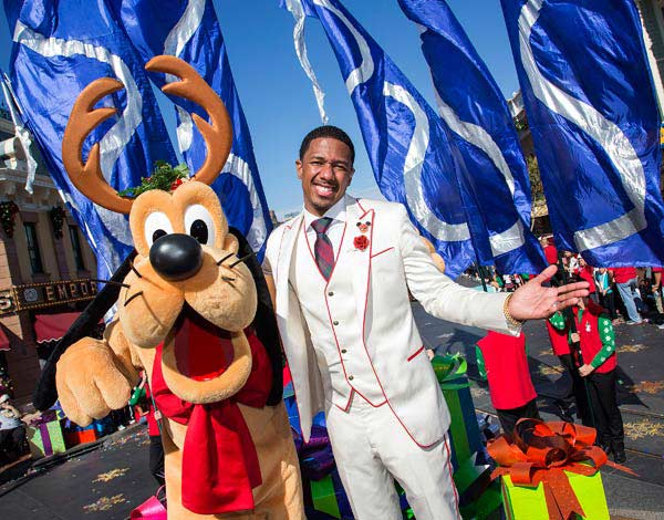 Host Nick Cannon meets Pluto during a break from taping the 'Disney Parks Christmas Day Parade' television special at Disneyland in Anaheim, California on Sunday, Nov. 10, 2013. 'Disney Parks Christmas Day Parade' airs Dec. 25, 2013 on ABC.